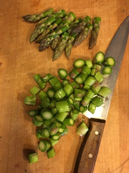 """Chop asparagus, saving the tops for garnish"""
