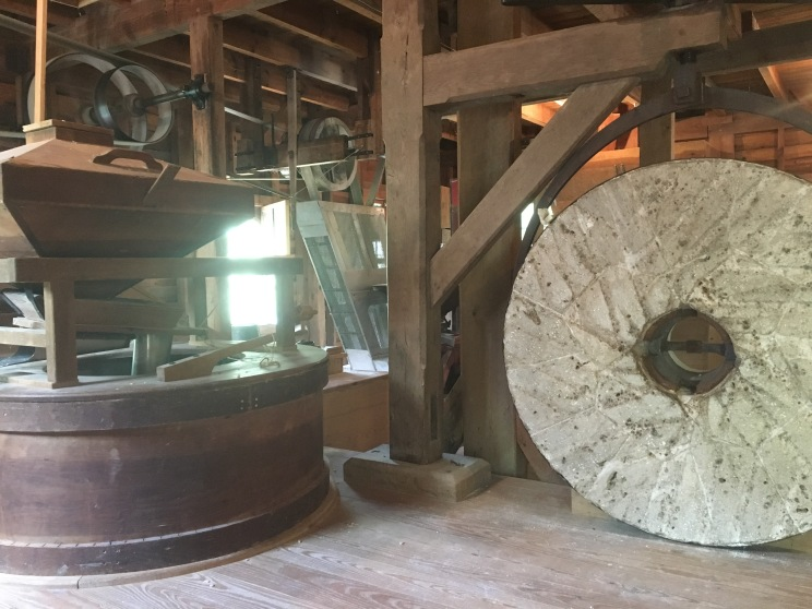 Giant grinding stone powered by water wheel,